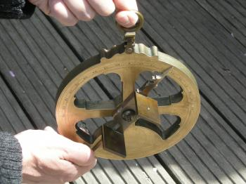Holding the astrolabe for observations.