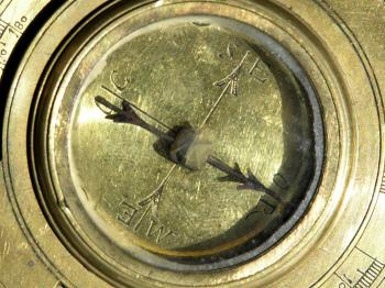 A close-up of the compass shows circular wear at the centre of the glass.