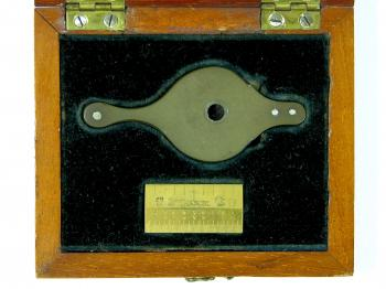A close-up of the box contents, showing the loupe and inch.